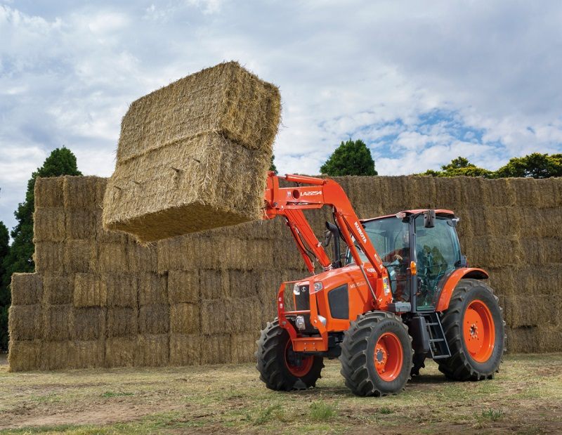 M-GX 135 Kubota Tractor with loader lifting bale