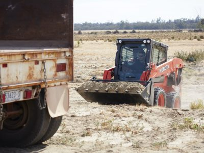 Mini Skid Steer loader dumping in truck