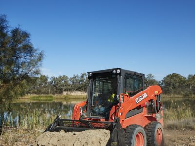 Kubota SSV skid steer carrying load of dirt