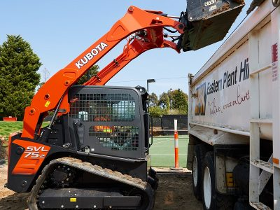 Kubota SVL track loader dumping bucket in truck